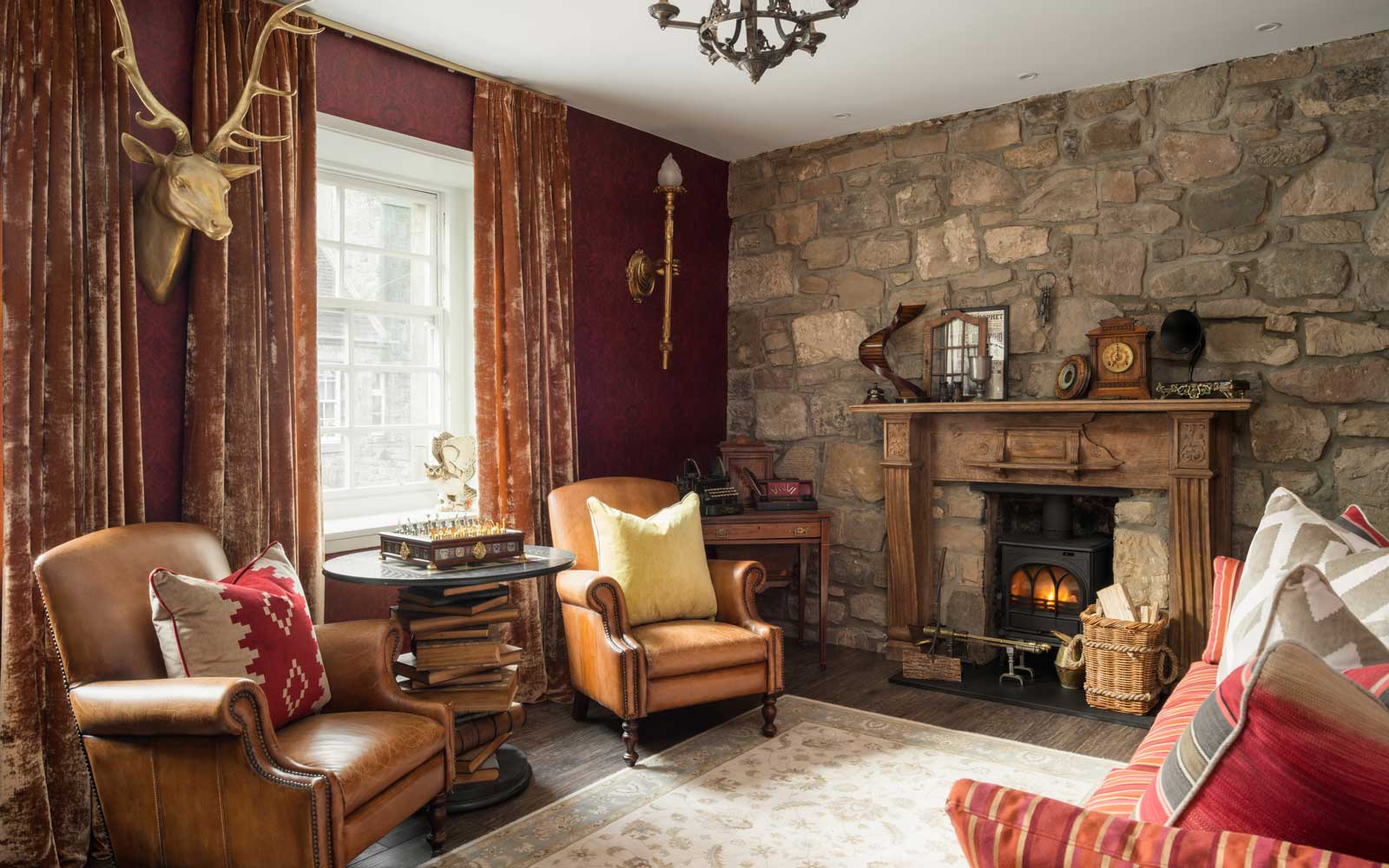 The living room has been designed to look like the Gryffindor common room. See Centre Press story CPPOTTER; Harry Potter fans now have the chance to spend a night at Hogwarts -- after a luxury apartment dedicated to the much-loved films opened to visitors. Situated in the Scottish Capital -- the birthplace of J.K Rowling's Harry Potter books -- the magical apartment is the brainchild of Hogwarts superfan Yue Gao. Canongate Luxury Apartment, which overlooks Edinburgh's Royal Mile, has a master bedroom with a Gryffindor dormitory theme. The flat, which is available to rent all year round, comes with a four-poster bed and has a ceiling which makes a beautiful illusion of floating candles. A second, smaller double room has been decked out to look like a carriage from the Hogwarts Express.