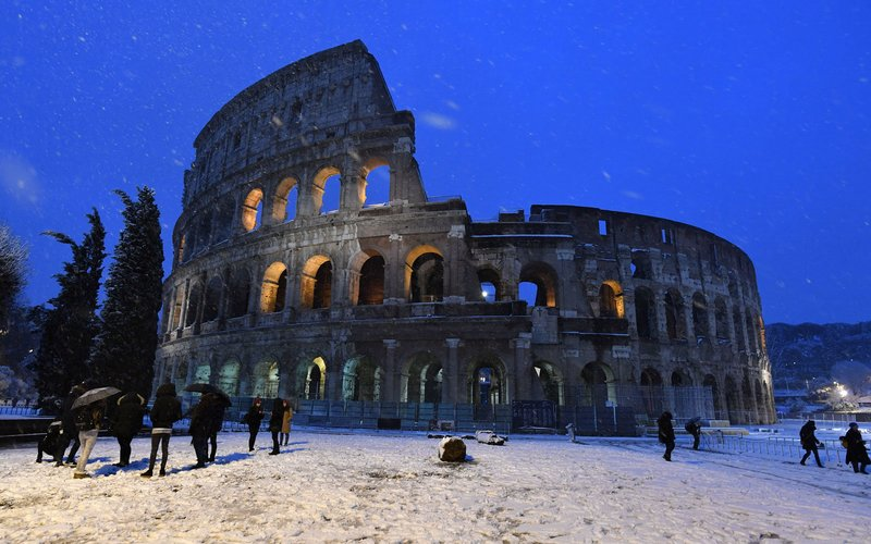 People walk in the snow near the Colosseum in Rome on February 26, 2018.    / AFP PHOTO / TIZIANA FABI        (Photo credit should read TIZIANA FABI/AFP/Getty Images)