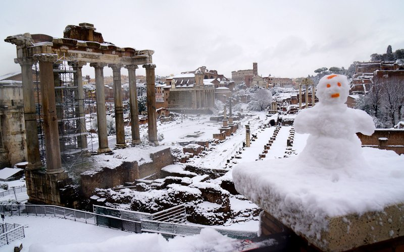 A picture taken in Rome on February 26, 201 shows a view of the Ancient Forum and a snowman during a snowfall.     / AFP PHOTO / Vincenzo PINTO        (Photo credit should read VINCENZO PINTO/AFP/Getty Images)