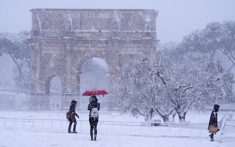 Tourists visit the Arch of Constantine during a snowfall in Rome on February 26, 2018.     / AFP PHOTO / Vincenzo PINTO        (Photo credit should read VINCENZO PINTO/AFP/Getty Images)