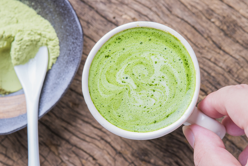 Hot green tea latte with matcha powder on wooden background.