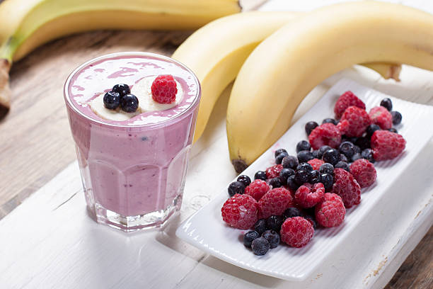 Smoothies of frozen raspberries, blueberries and banana with yogurt. Blueberries and raspberries on a white plate and a banana  on a wooden table..