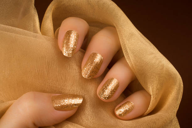 Female hand with glittered golden nails is holding a golden luxury textile material on brown background.