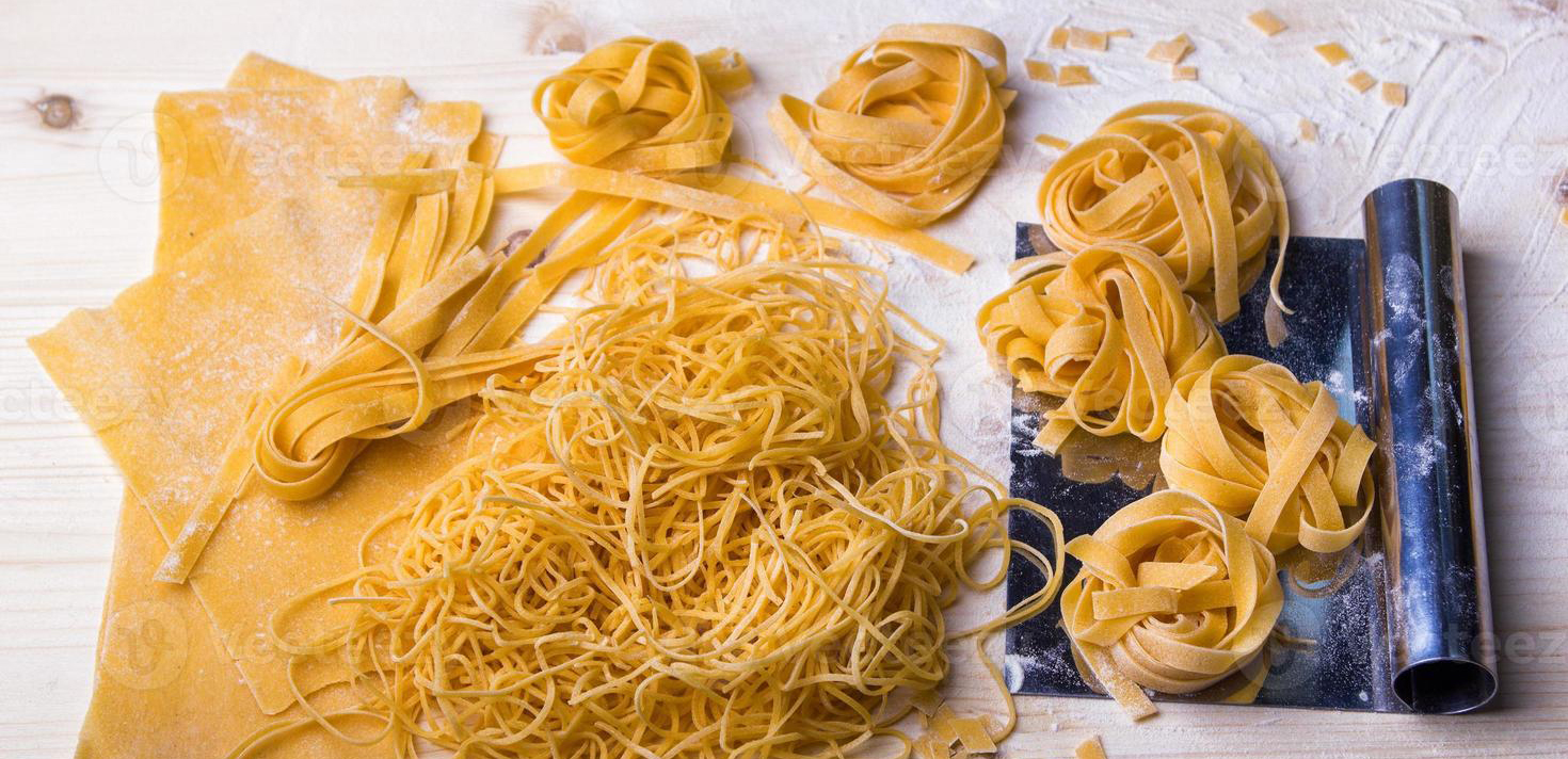 homemade-noodles-and-pasta-on-wooden-table-photo